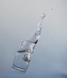 Vidrio altísimo con agua y el chapoteo Fotos de archivo