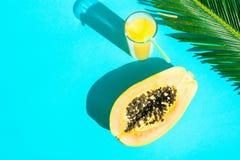 Vidrio alto de la endecha de la composición plana del arreglo con el fondo fresco de Juice Papaya Palm Leaf Blue de la fruta trop imagen de archivo libre de regalías