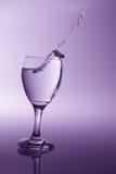 Vidrio con agua clara que cae al derramamiento con li de la parte posterior de la púrpura Foto de archivo libre de regalías