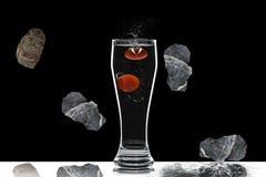 Vidrio con agua y piedras que caen en un fondo negro fotos de archivo