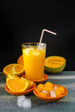 Vidrio con el jugo melón-anaranjado presionado helado fresco y f fresca fotografía de archivo libre de regalías