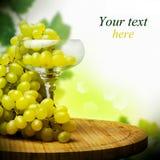 Vidrio con el manojo de uvas maduras Foto de archivo
