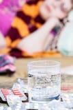 Vidrio con el medicamento y la pila de píldoras en la tabla Imagen de archivo libre de regalías