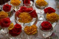 Vidrio con el ramo de rosas en un fondo coloreado foto de archivo
