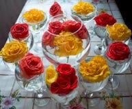Vidrio con el ramo de rosas en un fondo coloreado imágenes de archivo libres de regalías