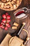 Vidrio con el vino, las botellas y el manojo de uvas, fondo de madera Fotos de archivo
