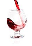 Vidrio con el vino que fluye Imagenes de archivo