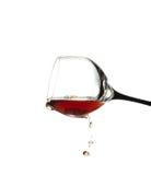 vidrio con el vino que fluye abajo de cierre para arriba aislado en un blanco Imagenes de archivo