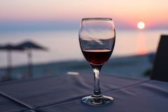 Vidrio con el vino rojo y la puesta del sol en la playa en el fondo concepto de las vacaciones del verano Fotografía de archivo libre de regalías
