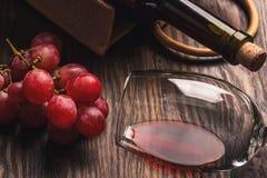 Vidrio con el vino, una botella y el manojo de uva madura, fondo de madera Fotografía de archivo