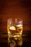 Vidrio con el whisky en la tabla de cristal Fotos de archivo
