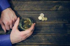 Vidrio con el whisky en una mano del ` s del hombre que miente en una tabla de madera fotos de archivo
