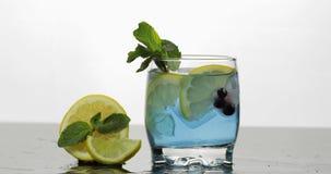 Vidrio con la bebida azul fr?a con las hojas de la menta, cal, lim?n, grosellas negras foto de archivo libre de regalías