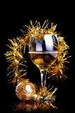 Vidrio con la bebida, una bola de la Navidad y malla. Imágenes de archivo libres de regalías