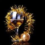 Vidrio con la bebida, una bola de la Navidad y malla. Imagen de archivo libre de regalías