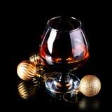 Vidrio con la bebida y las bolas de una Navidad Imagen de archivo libre de regalías