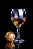 Vidrio con la bebida y una bola de la Navidad. Imagenes de archivo