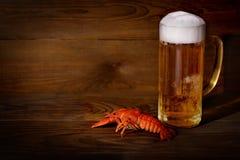 Vidrio con la cerveza y un cangrejo hervido en una tabla de madera Imagenes de archivo