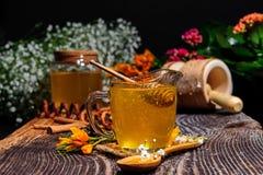 Vidrio con la miel en el fondo de madera Fotografía de archivo libre de regalías