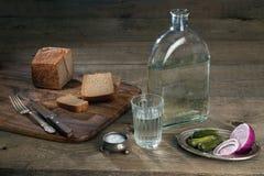 Vidrio con la vodka, los pepinos, la cebolla y el pan en una tabla de madera Imagen de archivo libre de regalías