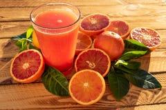 Vidrio con las frutas frescas anaranjadas de Juice Of Blood Oranges With Tiro al aire libre en la sol fotos de archivo