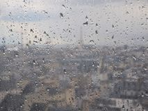 Vidrio con las gotas de agua, fondo urbano borroso, París, Francia imagen de archivo