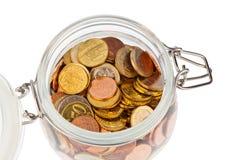 Vidrio con las monedas euro Imágenes de archivo libres de regalías