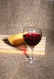 Vidrio con las uvas de vino rojo y los chees en la tabla de madera Fotografía de archivo