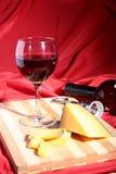 Vidrio con las uvas de vino rojo y los chees en la tabla de madera Fotos de archivo