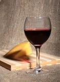 Vidrio con las uvas de vino rojo y los chees en la tabla de madera Imagen de archivo libre de regalías