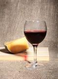 Vidrio con las uvas de vino rojo y los chees en la tabla de madera Imágenes de archivo libres de regalías
