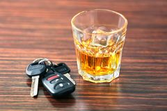 Vidrio con llaves del alcohol y del coche foto de archivo