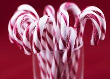 Vidrio con los bastones de caramelo de la Navidad foto de archivo