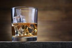 Vidrio con los cubos del whisky y de hielo imagen de archivo
