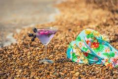 Vidrio con los zapatos helados de la bebida y de la playa en la playa en la playa entre los guijarros del mar La atmósfera del re Imagen de archivo