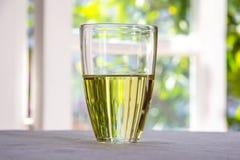 Vidrio con Olive Oil Placed On una tabla contra la ventana Fotos de archivo libres de regalías