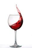 Vidrio con un chapoteo del vino rojo aislado en el fondo blanco Imagenes de archivo