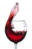 Vidrio con un chapoteo del vino rojo aislado en el fondo blanco Imagen de archivo