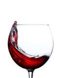 Vidrio con un chapoteo del vino rojo aislado en el fondo blanco Fotos de archivo libres de regalías