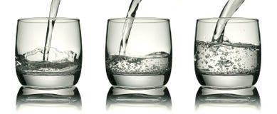 Vidrio con un chorro de agua Foto de archivo libre de regalías