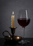 Vidrio Copa de vino y vela rojas delante de la pared de piedra del granito Imagenes de archivo