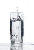 Vidrio de agua con el chapoteo Fotos de archivo libres de regalías