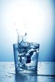 Vidrio de agua con el chapoteo imagen de archivo