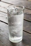 Vidrio de agua con hielo en la tabla de madera Imagenes de archivo