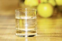 Vidrio de agua con la fruta en fondo Imagen de archivo libre de regalías