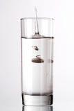 Vidrio de agua con la píldora Fotografía de archivo libre de regalías