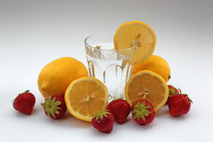 Vidrio de agua con los limones y las fresas en el fondo blanco Imagenes de archivo