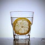 Vidrio de agua con una rebanada del limón imagen de archivo libre de regalías