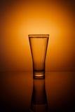 Vidrio de agua en fondo anaranjado Foto de archivo