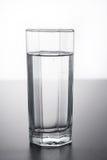 Vidrio de agua en la tabla con la reflexión imagenes de archivo